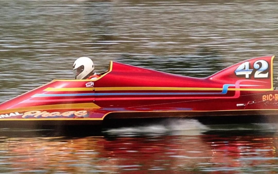 red speed boat with driver wearing a white helmet