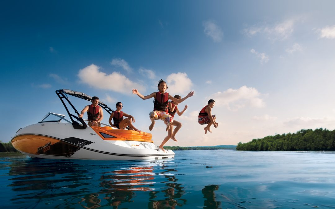kids jumping off back of boat